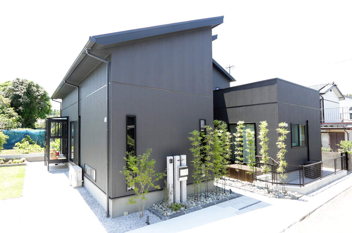 黒の外壁と飛び石と竹の似合うオシャレな外観に